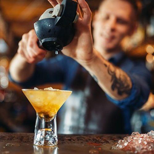 barman-squeezes-lemon-into-glass-full-ice