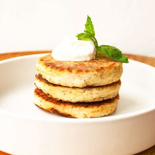 cottage-cheese-pancakes-curd-fritters-stack-with-sour-cream-mint-decorated-with-almond-coconut-flour-gluten-free-white-plate-close-up-view-healthy-eating-breakfast-selective-soft-focus