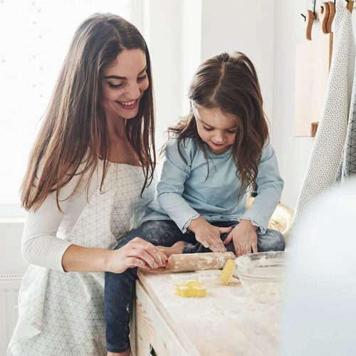 front-view-happy-daughter-mom-are-preparing-bakery-products-together-little-helper-kitchen